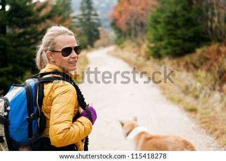 Woman hiking in mountains with akita dog, Karkonosze Mountain Range. Happy smiling hiker on autumn footpath in forest. - stock photo