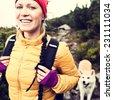 Woman hiking in mountains with akita dog, vintage instagram style photography outdoors in beautiful nature, Karkonosze Mountain Range, Poland - stock photo