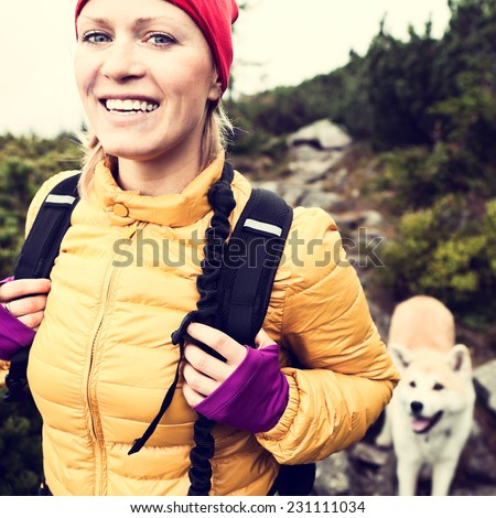 Woman hiking in mountains with akita dog, vintage instagram style photography outdoors in beautiful nature, Karkonosze Mountain Range, Poland - stock photo