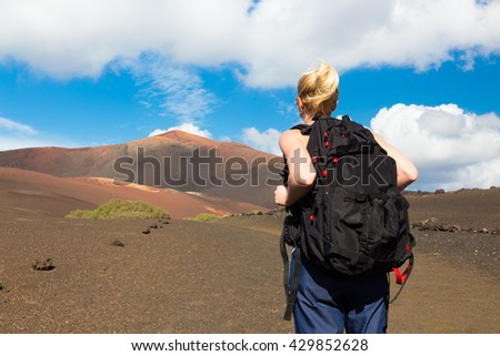 Woman hiking in nature can see the peak of Timanfaya volcano, nearly made it to top. - stock photo