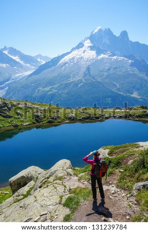 Woman hiking in the mountains on a tourist track - stock photo