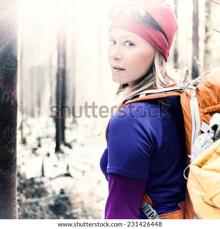 Woman hiking in white winter vintage forest, backlight by morning sunlight rays, recreation and healthy lifestyle outdoors in nature. Beauty blond retro hiker backpacker looking at camera on sunset. - stock photo