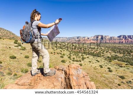Woman hiking looking at map - stock photo