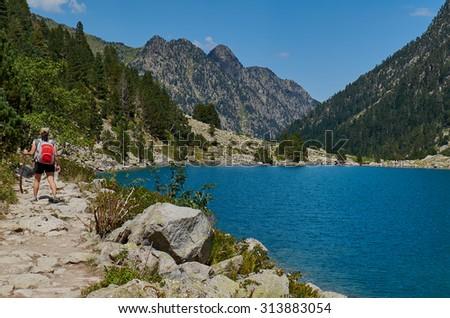 Woman hiking near a mountain Lake  - stock photo
