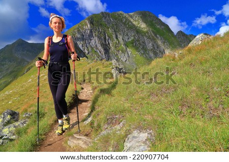 Woman hiking on green mountain trail under blue sky - stock photo