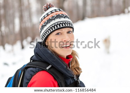 Woman hiking on snow in white winter forest. Recreation and healthy lifestyle outdoors in nature. Beauty blond looking at camera on sunset. - stock photo