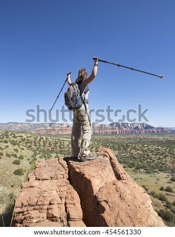 Woman hiking raises arms in celebration - stock photo