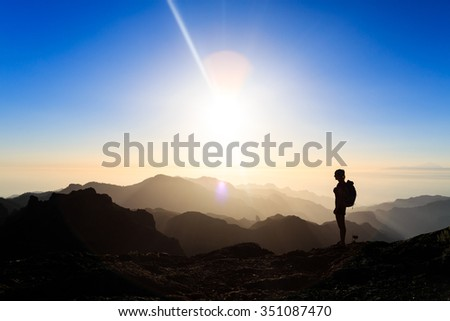 Woman hiking silhouette in mountains, sunset and ocean. Female hiker on mountain top looking at beautiful night sunset inspirational landscape on Gran Canaria, Canary Islands. - stock photo