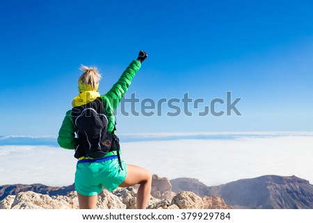Woman hiking success with arms outstretched on mountain top. Motivation in inspirational landscape on island and ocean. Female hiker with arms up on mountain top looking at beautiful view on Tenerfie. - stock photo