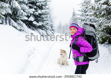 Woman hiking trekking in winter woods with akita dog. Recreation fitness and healthy lifestyle outdoors in beautiful snowy nature. Motivation and inspirational white winter landscape. - stock photo