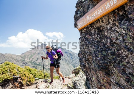 Woman hiking with backpack in mountains, Bocca Avartoli 1898m above see level. Trekking in high mountains and reaching a pass. Selective focus on sign. - stock photo