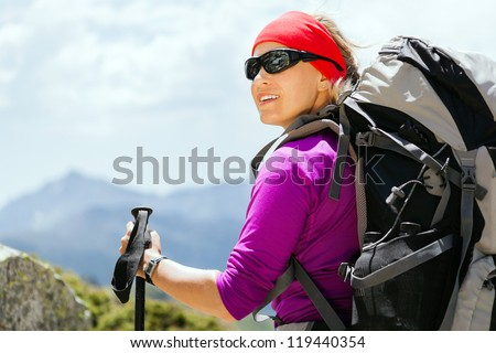 Woman hiking with backpack in mountains, Corsica France. Success and achievement, sport, exercising outdoors in summer nature