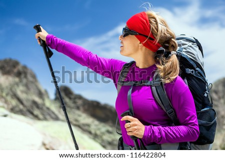 Woman hiking with backpack in mountains, mountaineering and trekking in Corsica France - stock photo
