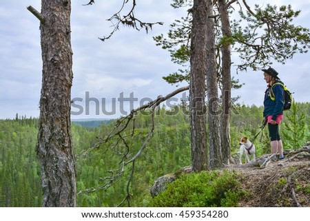 Woman hiking with dog in Lapland Finland
