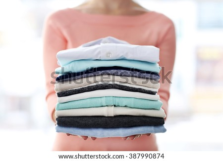 Woman hold clothes pile, close up - stock photo