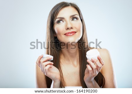 Woman hold cosmetic cream. Beautiful face young model. Isolated portrait. - stock photo
