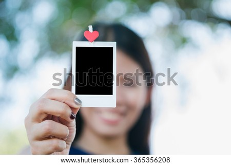 Woman hold  photo instant on hand. Blank instant photo and red clip paper heart. relationship concept.