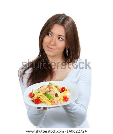 Woman hold plate of diet Italian Shrimp spaghetti vongole pasta with bell pepper, origan, basil and creamy Alfredo sauce and tasting one tomato isolated on a white background