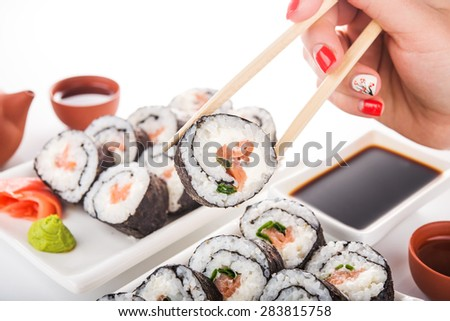 Woman hold sushi roll on background - stock photo