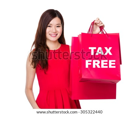 Woman hold with paper bag and showing tax free - stock photo
