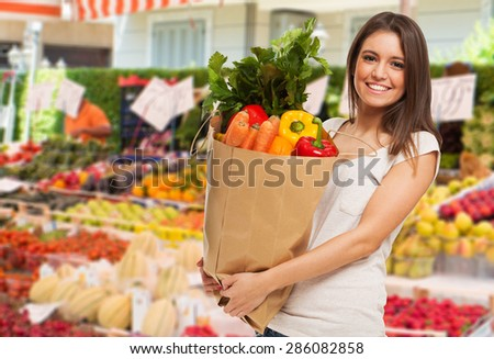 Woman holding a bag in a fruit and vegetable outdoor market - stock photo
