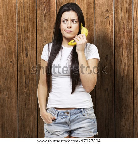 woman holding a banana as a telephone against a wooden background