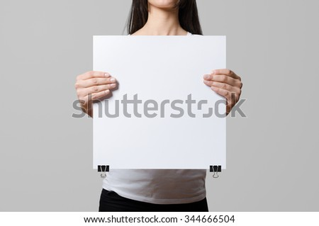 Woman holding a blank poster, square 35x35, mockup. - stock photo