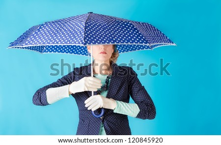 Woman holding a blue polk a dot umbrella retro feel