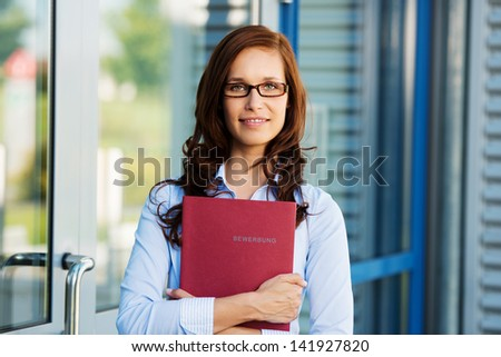Woman holding a book against the door background - stock photo