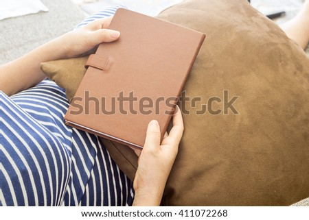 Woman holding a  book on the sofa