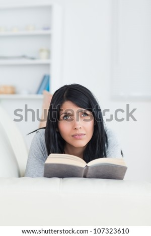 Woman holding a book while relaxing on a sofa in a living room