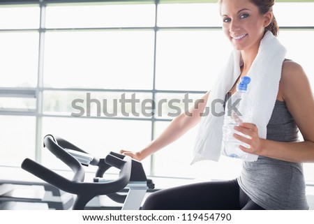 Woman holding a bottle of water and riding an exercise bike - stock photo