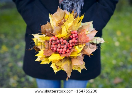 Woman holding a bouquet of maple leaves and mountain ash. - stock photo