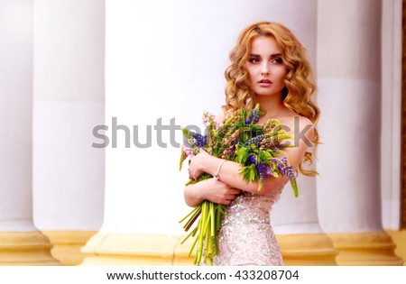 woman holding a bouquet of wildflowers near the columns
