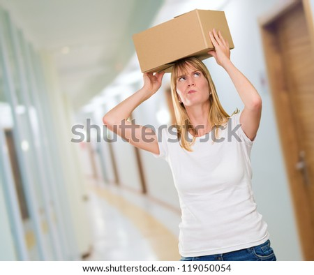 woman holding a box on her head in a passage way - stock photo