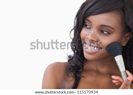Woman holding a brush while looking against white background - stock photo