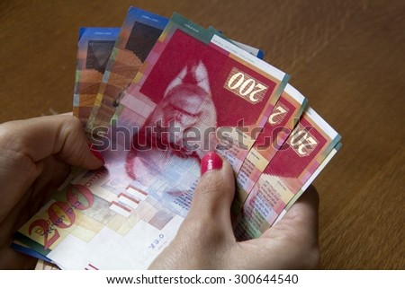 Woman holding a bunch of Israeli New Sheqel banknotes in her hands.
