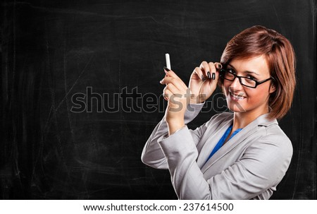 Woman holding a chalk in front of a blackboard - stock photo