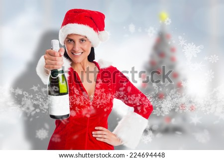 Woman holding a champagne bottle against blurry christmas tree in room - stock photo
