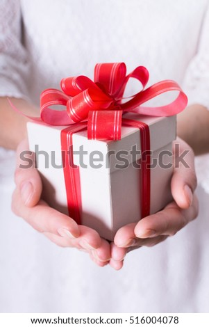Woman holding a christmas gift in hand