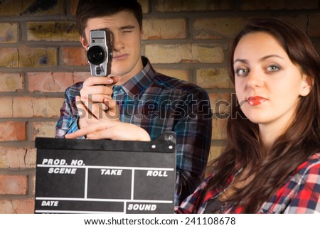 Woman holding a clapperboard ready for the videographer behind her to commence action and start filming or recording, young man holding retro camera - stock photo
