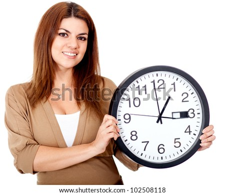 Woman holding a clock and smiling - isolated over a white background - stock photo