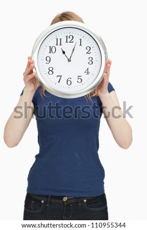 Woman holding a clock in front of her face against a white background