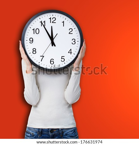 Woman holding a clock over face against orange background. Time concept - stock photo