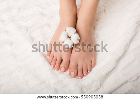 Woman holding a cotton flower. Pedicure concept