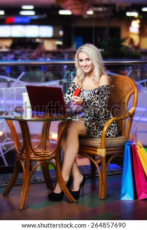 Woman holding a credit card and using laptop for on-line shopping. - stock photo