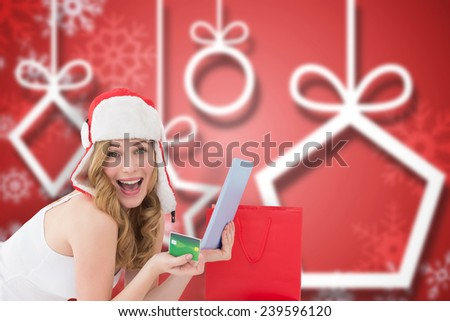 Woman holding a credit card surrounded with gifts against blurred christmas background - stock photo