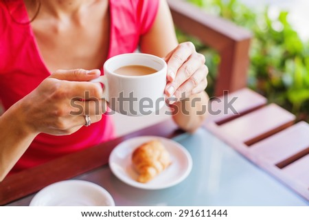 woman holding a cup of coffee - stock photo