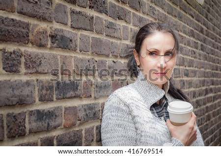 Woman holding a cup of coffee while leaning against a brick wall - stock photo