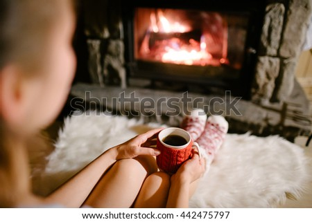 Woman holding a cup of tea by the Christmas fireplace. Woman relaxes by warm fire with cup of hot drink and warming up her feet in woollen socks. Close up on feet. Winter, Christmas holidays concept.